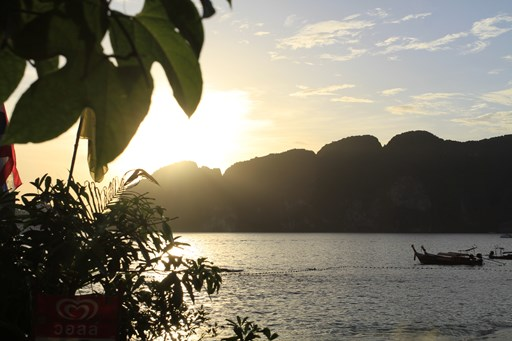 evening-thailand-water-in-sunlight-dark-mountains-on-phi-islands-tree-leaves-foreground-small-kayak-boat-in-ocean-stock-image1.jpg
