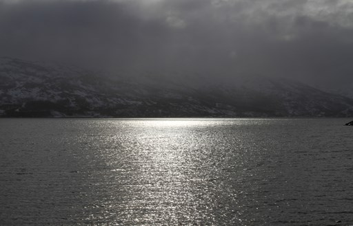 grey-water-sunny-reflection-mountains-far-away-view-cold-frozen-air-white-clouds-norwegian-weather-nature-shore-stock.jpg
